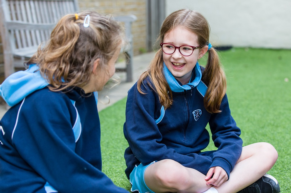 two school girls chatting to eachother outside on the grass
