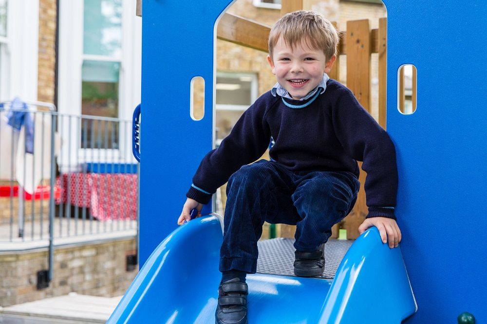 young smiling boy going down a slide
