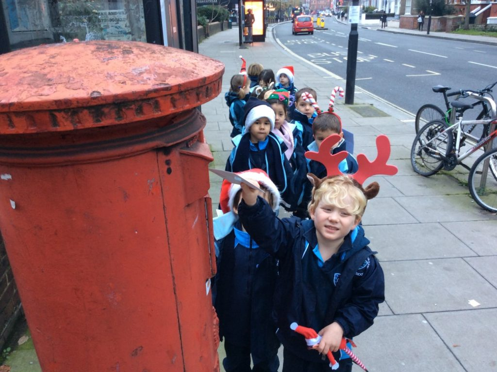 Children posting letters to Santa in a row at the postbox