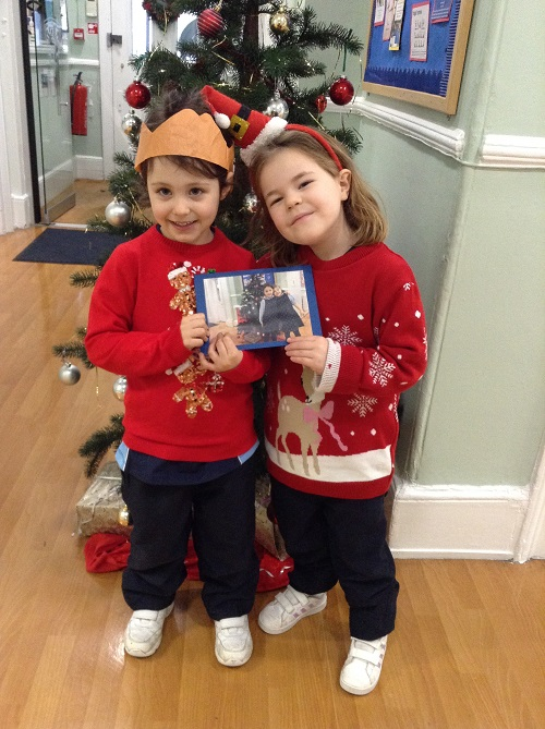 two young children wearing christmas jumpers