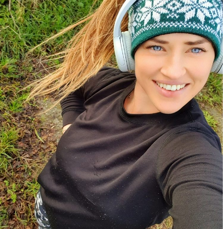 young woman taking a selfie wearing headphones and running gear