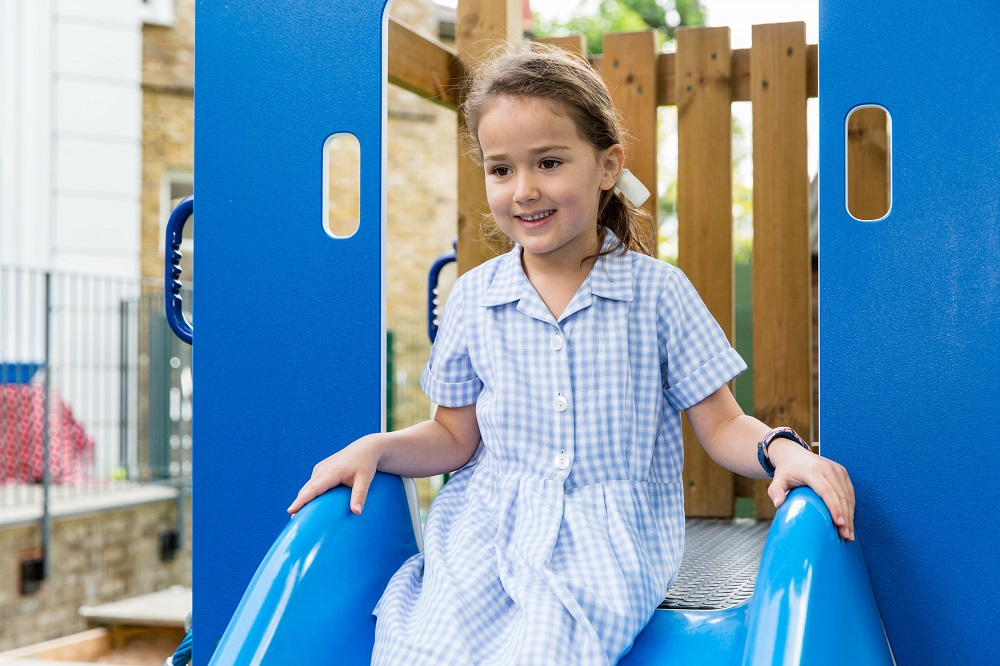 young girl wearing blue school dress sitting at the top of a slide