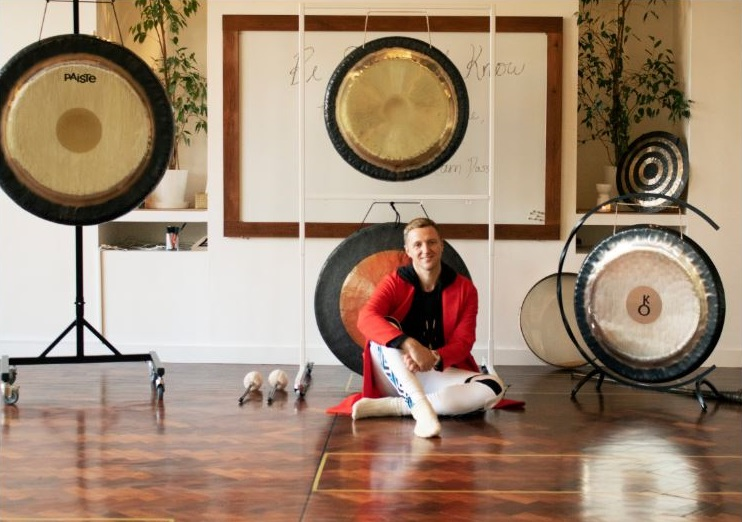 A teacher with a range of drums and cymbals around them