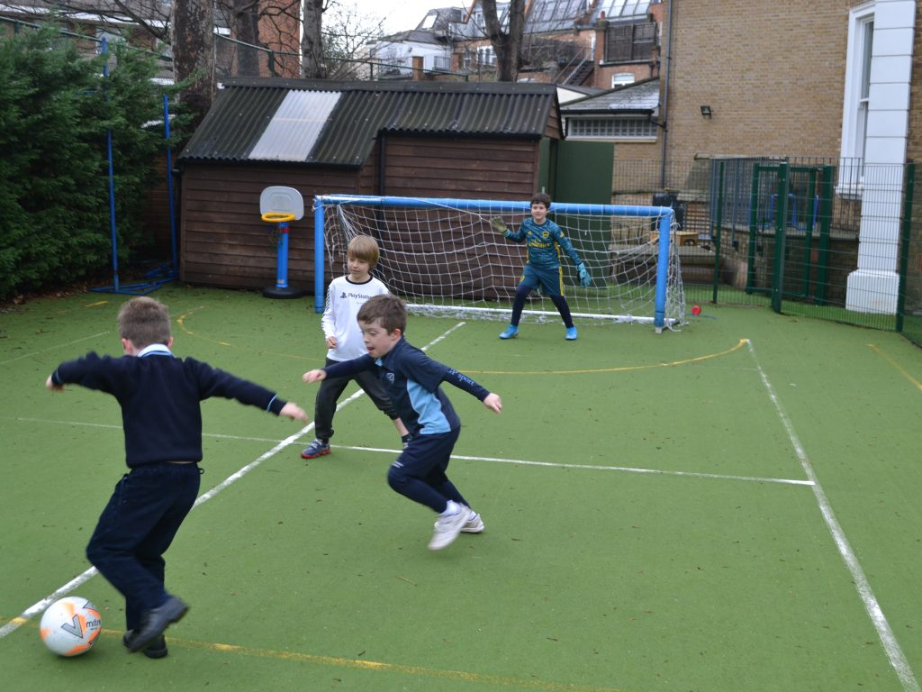 Schoolboys playing football on the astro turf pitch