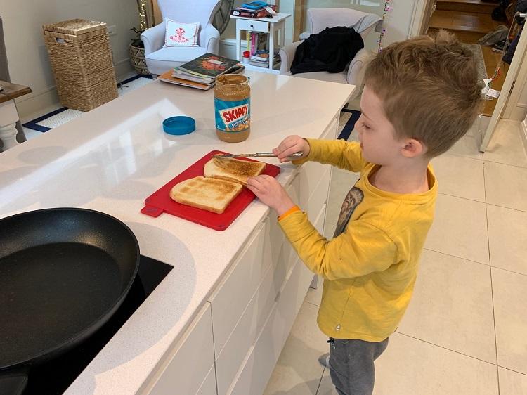 boy making peanut butter toast