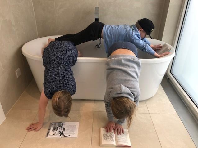 3 children reading in bath tub for world book day