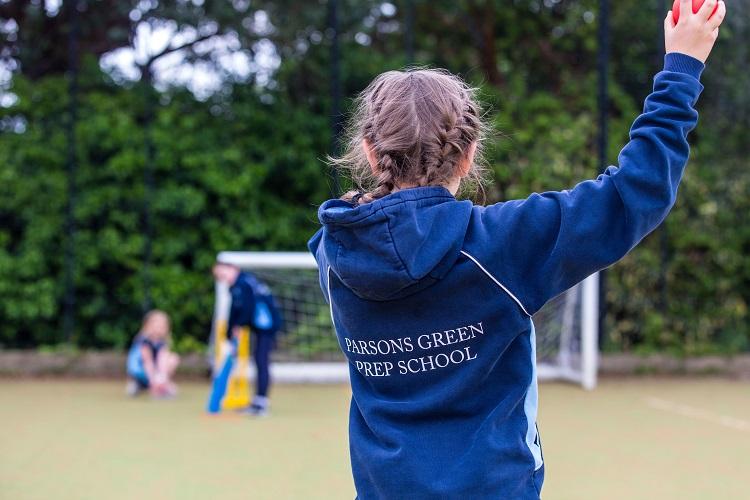 girl in Parsons Green Prep School hoodie throwing a cricket ball