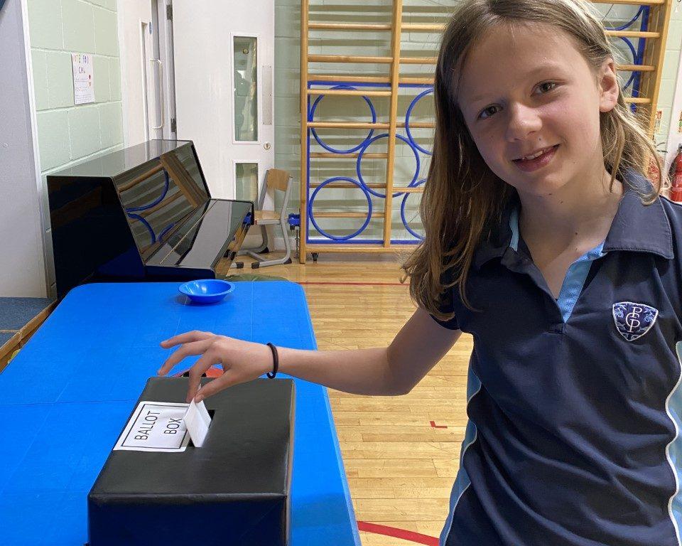 school girl at ballot box