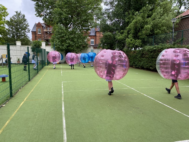 Children trying out zorbing or bubble football